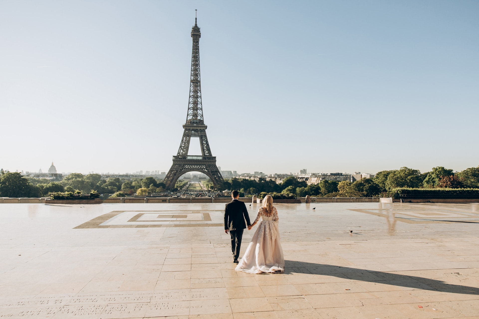 woman-and-man-walking-in-park-in-front-of-eiffel-tower-1488315